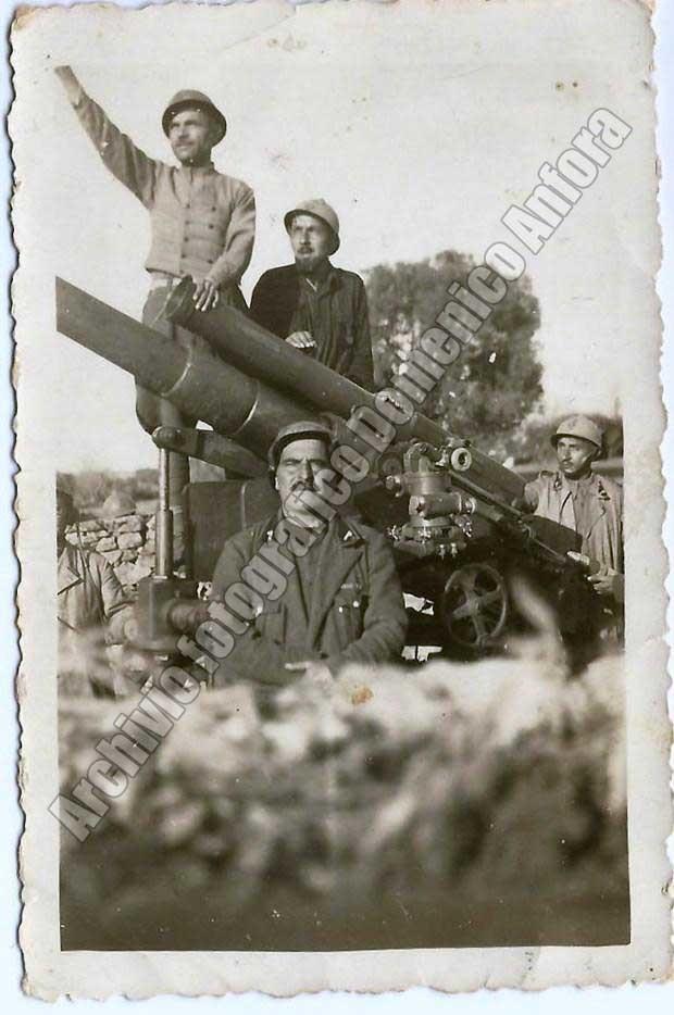 Il vicecaposquadra della Milizia Contraerea Colombo Tabarrini. Alle spalle un cannone in postazione presso l'aeroporto di S. Pietro.